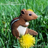 Chipmunk sitting on the lawn with dandelions.